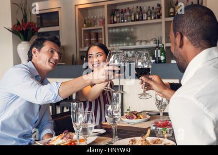 Friends clinking wine glasses in restaurant - Stock Photo