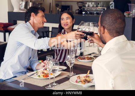 Couple clinking glasses in restaurants with friends - Stock Photo