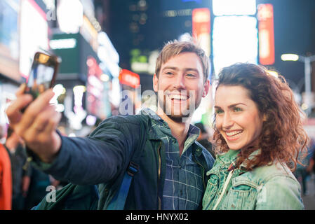 Young couple taking selfie in Times Square, New York City, New York, USA - Stock Photo