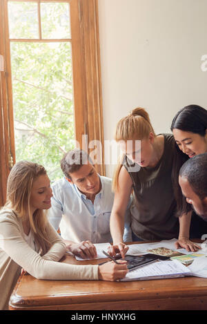 Colleagues looking at digital tablet together in office - Stock Photo