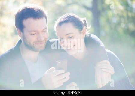 Couple using mobile app on smartphone for navigation - Stock Photo