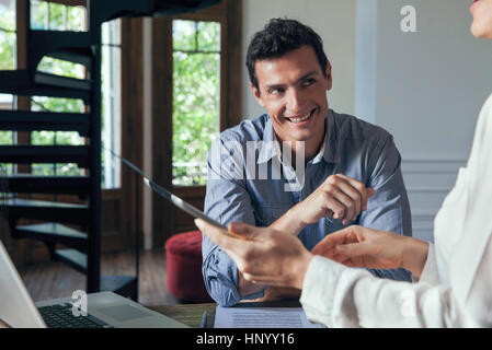 Man smiling during meeting with colleague - Stock Photo