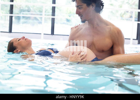 Pregnant woman exercising with help of fitness trainer in swimming pool - Stock Photo