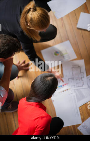 Colleagues discussing blueprint and color swatches - Stock Photo