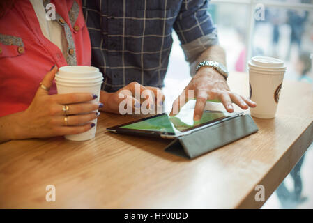 Couple using digital tablet in coffee shop, cropped - Stock Photo