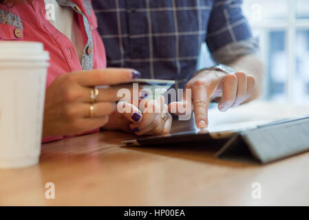 Couple shopping online using digital tablet - Stock Photo