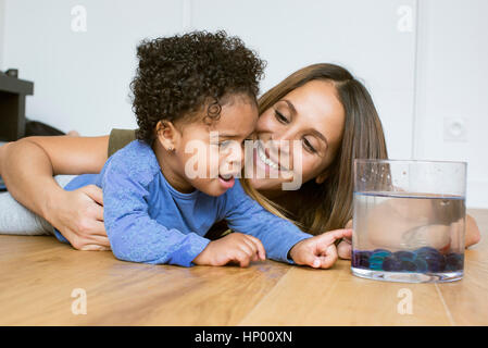 Mother and toddler daughter looking at pet goldfish - Stock Photo