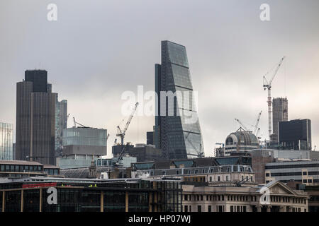 Tower cranes on the skyline of construction sites in the City of London with iconic modern architecture skyscrapers - Stock Photo