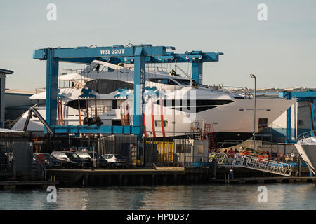 A crane lifts a Sunseeker luxury yacht out of the water in Poole harbour Dorset - Stock Photo