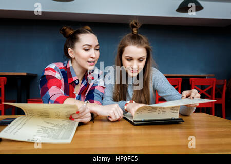 happy girl friends have cup of coffee in modern city restaurant. - Stock Photo