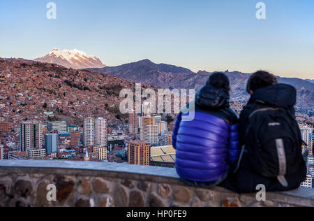 Couple and Panoramic view of the city, in background  Illimani mountain 6462 m, La Paz, Bolivia - Stock Photo