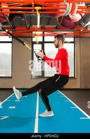 white curly bearded sporty man exercising with fitness straps in gym Crossfit instructor at the gym doing Excersise. - Stock Photo