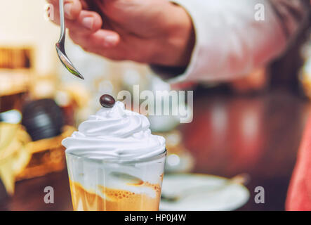 Barista is decorated  of a chocolate sweets on the cream in a mug of cappuccino.  Beautiful close-up background. - Stock Photo