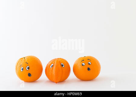 Fresh oranges with funny faces in front of white background. One orange has a huge nose - Stock Photo