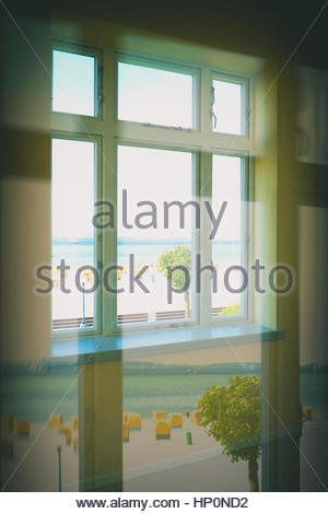 Window reflection beach summer hooded beach chairs - Stock Photo