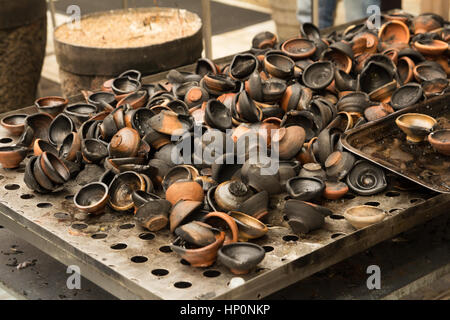 burned clay oil lamps in temple - Stock Photo
