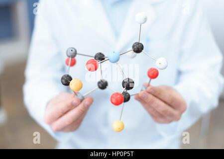 scientist in white coat holding molecular model - Stock Photo