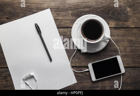 Top view of coffe ,notepad with pen and phone on wooden table - Stock Photo
