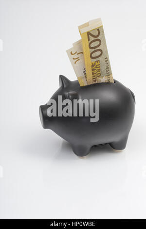 Black Piggy bank with 200 Euro banknote placed in coin slot. Metaphor for personal savings, or EU / European / Brussels - Stock Photo