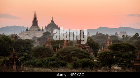Sunset in Bagan with pink sky above some of the stupas and Temples that cover the land in this part of Myanmar - Stock Photo