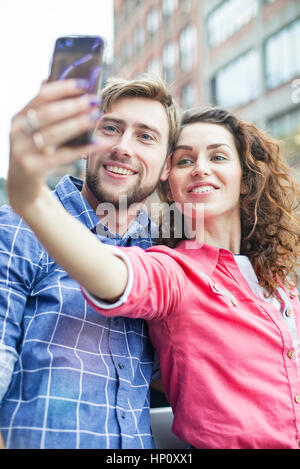 Couple taking a selfie together outdoors - Stock Photo