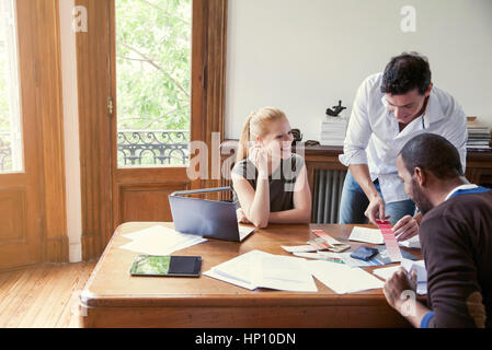 Designers looking at color swatches in office - Stock Photo