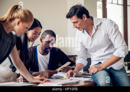 Interior decorator looking at color swatches with clients - Stock Photo