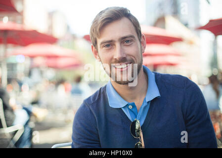 Young man smiling outdoors, portrait - Stock Photo
