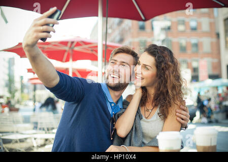 Couple posing for a selfie at outdoor cafe - Stock Photo