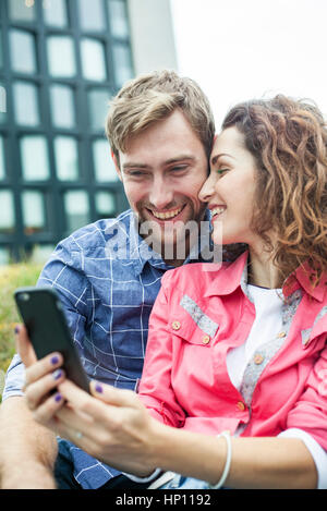 Couple using smartphone to take a selfie - Stock Photo