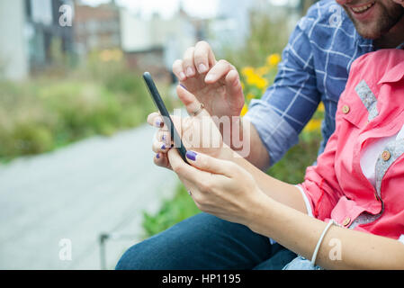 Couple using smartphone together outdoors - Stock Photo