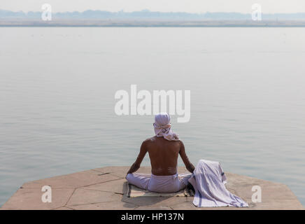 A man meditates on the Ganges River in Varanasi, one of India's holiest cities. Varanasi is a popular destination - Stock Photo