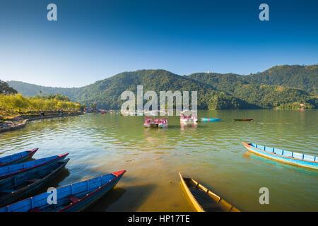 Rowboats lined up at Fewa Lake (Phewa Tal), Pokhara, Nepal with Machhapuchre in the background - Stock Photo