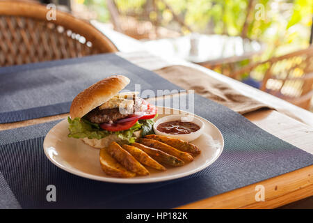 A Bleu (Blue) cheese hamburger with fries and barbecue sauce on a cafe table - Stock Photo
