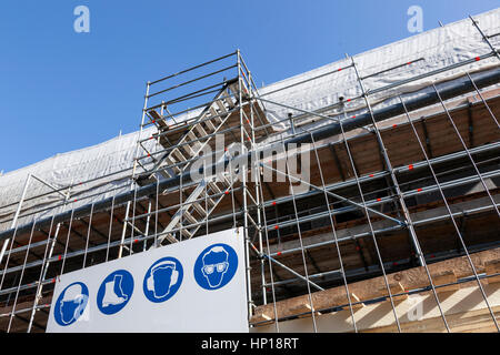 scaffolding with stairs under blue sky on new housing facility in the netherlands and arning signs - Stock Photo
