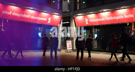 Pedestrians walk past a banner advertising the 67th Berlinale Film Festival near the Berlinale Palace in central - Stock Photo