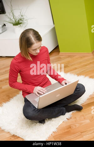 Model release , Junge Frau sitzt mit Laptop in Wohnraum - young woman with laptop - Stock Photo