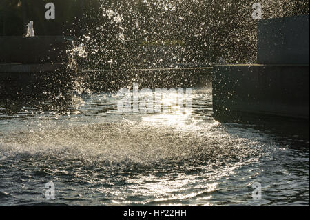 fragment of fountain water drops in the air. On the Sunset. - Stock Photo