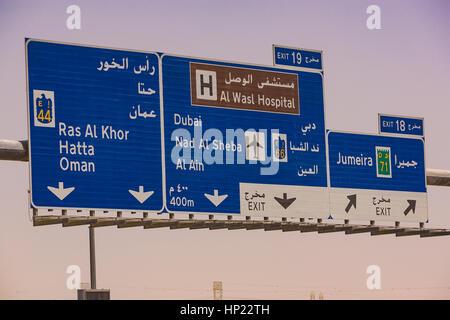 DUBAI, UNITED ARAB EMIRATES - Road sign over highway. Bilinigual sign in arabicd and english. - Stock Photo