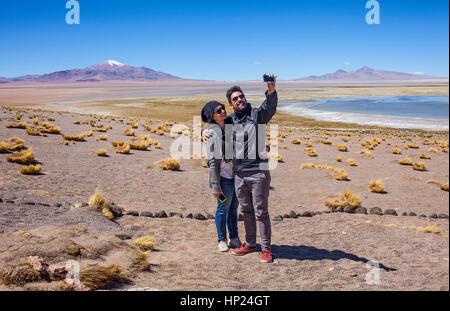 Tourists, couple, man, woman,  selfie, in Salar de Tara, salt flats, Altiplano,Puna, Atacama desert. Region de Antofagasta. - Stock Photo