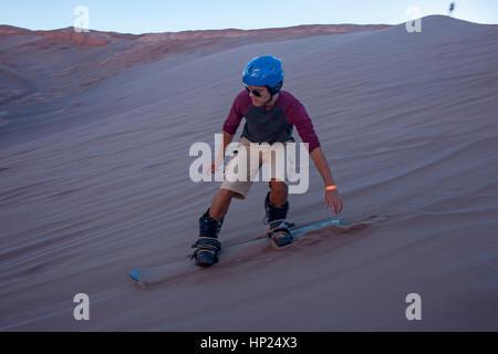 Sand boarding in the dune, in Duna Mayor (Greater Dune), in Valle de la Muerte (Valley of the Death), Atacama desert. - Stock Photo