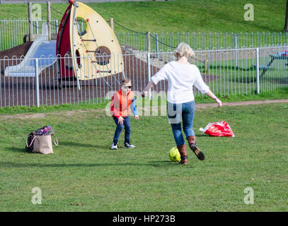 A mother and son play football in the park. - Stock Photo