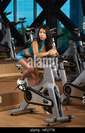 Girl doing bicycle exercises in fitness gym. Young pretty woman sit on bike gym - Stock Photo