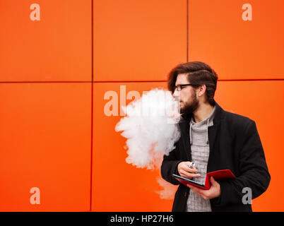 Young hipster man with a beard and glasses smokes an electronic cigarette. He holds a tablet pc. Youth fashion. - Stock Photo
