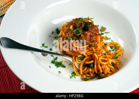 Spaghetti puttanesca with fork served in a white dish - Italian recipe with garlic, olive oil, anchovies, olives, - Stock Photo