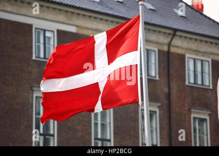 Waving Danish flag on the mast in Copenhagen, Denmark - Stock Photo