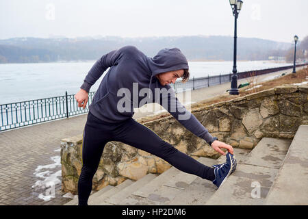 Young athlete doing workout running stretching before running in - Stock Photo