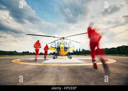 Alarm for the air rescue service. Team of rescuers (paramedic, doctor and pilot) running to the helicopter on the - Stock Photo