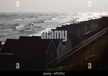 Beach huts along the seafront on Southwold, Norfolk beach in winter with a rough sea in the background. - Stock Photo
