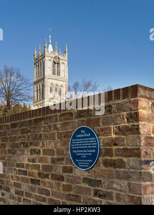 Heritage sign marking the boundary wall of the ancient London Road from Melton Mowbray with St. Mary's Church tower - Stock Photo